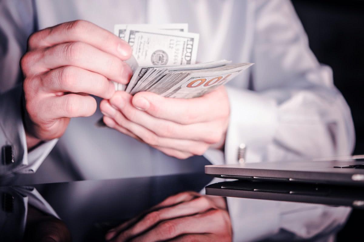 liczenie pieniędzy na tle laptopa